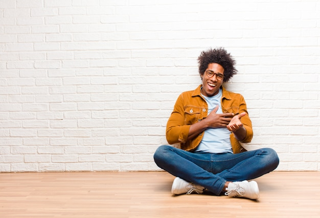 Young black man feeling happy and in love, smiling with one hand next to heart and the other stretched up front sitting on the floor at home