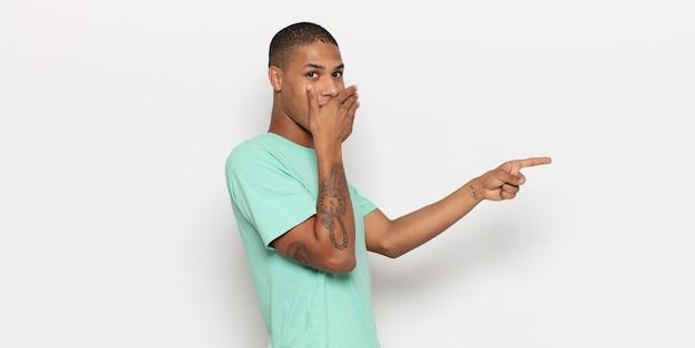 젊은 흑인 남자가 행복하고 충격적이며 놀란 느낌, 손으로 입을 덮고 측면 복사 공간을 가리키는