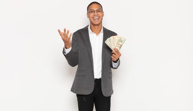 젊은 흑인 남자가 행복하고 놀랍고 쾌활한 느낌, 긍정적 인 태도로 웃고 솔루션이나 아이디어를 실현합니다.