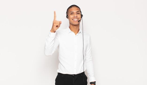 アイデアを実現した後、元気に指を上げて、幸せで興奮した天才のように感じる若い黒人男性、エウレカ!