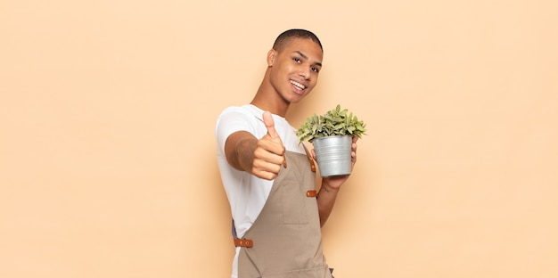 誇りに思って、のんきで、自信を持って幸せに感じ、親指を立てて前向きに笑っている若い黒人男性
