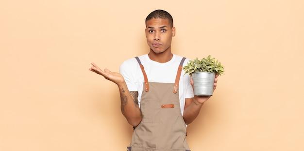 젊은 흑인 남자가 의아해하고 혼란스럽고 의심스럽고 가중하거나 재미있는 표현으로 다른 옵션을 선택하는 느낌