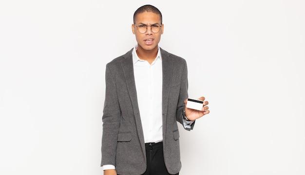 젊은 흑인 남자가 의아해하고 혼란스러워하며 예기치 않은 것을보고 멍청하고 기절 한 표정으로