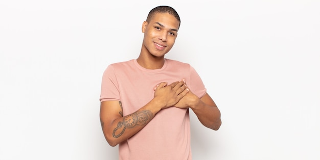 Young black man feeling romantic, happy and in love, smiling cheerfully and holding hands close to heart