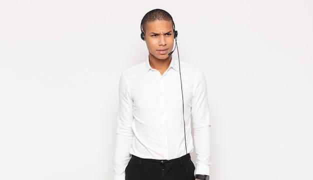Молодой темнокожий мужчина грустит, расстроен или зол, смотрит в сторону с негативным отношением и хмурится в знак несогласия.