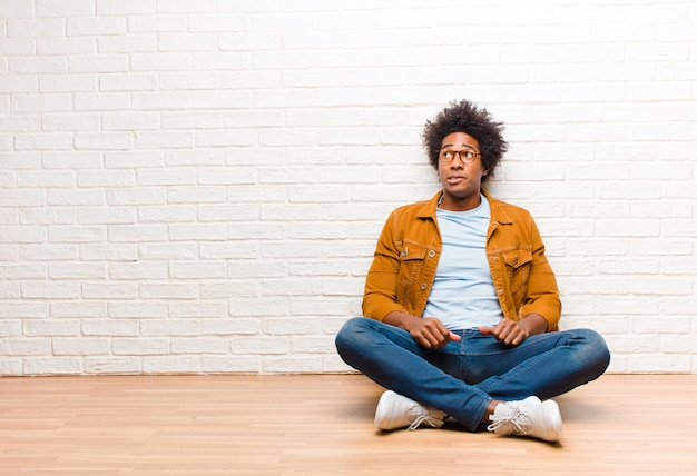 若い黒人男性が自宅の床に座って口を開けて側を見ていると、ショックを受けて、幸せで、驚いて驚いた