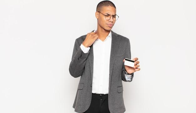 젊은 흑인 남자가 스트레스를 받고, 불안하고, 피곤하고, 좌절감을 느끼고, 셔츠 목을 당기고, 문제로 좌절감을 느낍니다.