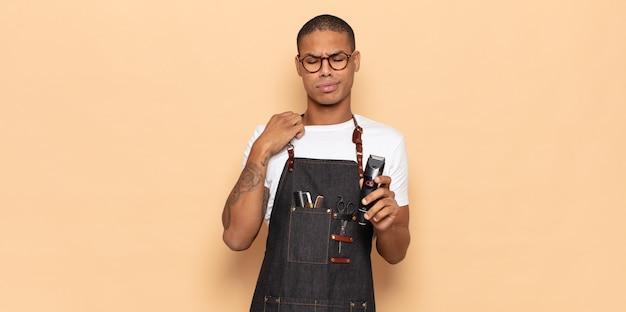 若い黒人男性は、ストレス、不安、疲れ、欲求不満を感じ、シャツの首を引っ張って、問題で欲求不満に見えます