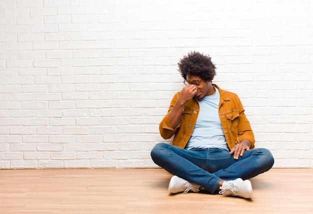 若い黒人男性がストレスを感じ、不幸で不満を感じ、額に触れ、家の床に座っている激しい頭痛の片頭痛に苦しんでいる