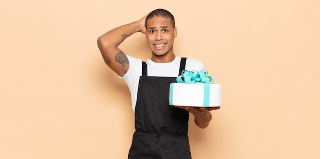 若い黒人男性は、頭に手を置いて、ストレス、心配、不安、または恐怖を感じ、誤ってパニックに陥る