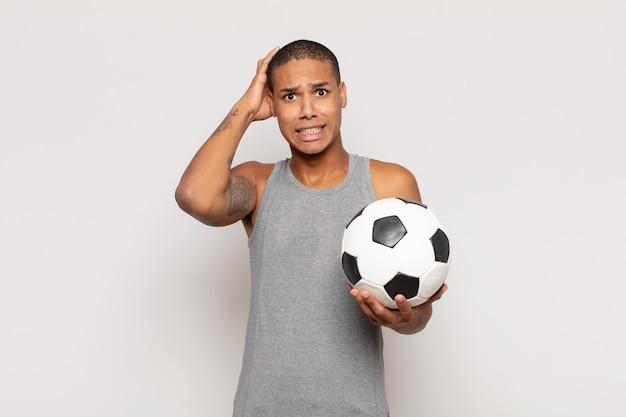 Молодой темнокожий мужчина, чувствуя стресс, беспокойство, беспокойство или испуг, с руками за голову