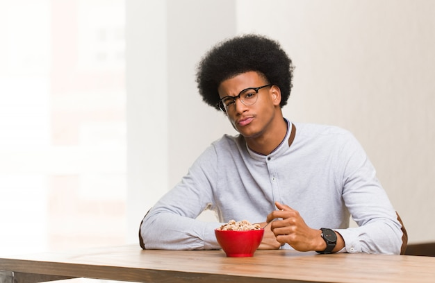 Young black man having a breakfast crossing arms relaxed