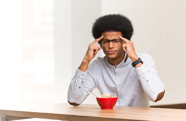 Young black man having a breakfast doing a concentration gesture