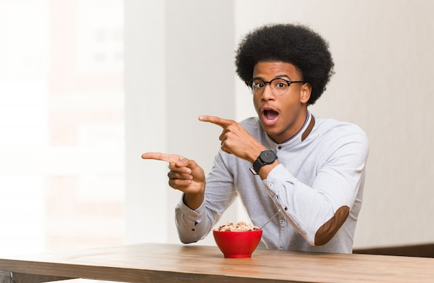 Young black man having a breakfast pointing to the side with finger