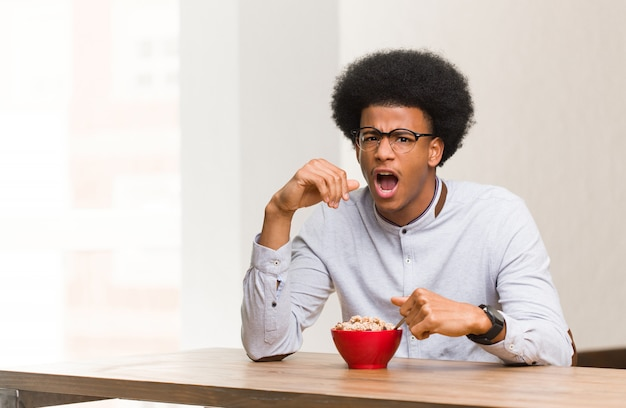 Young black man having a breakfast screaming very angry and aggressive