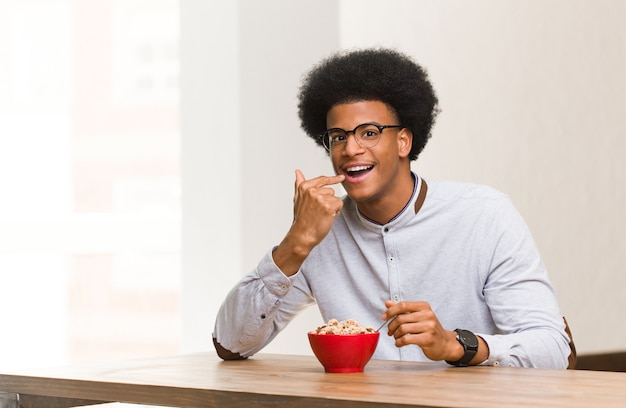 Young black man having a breakfast smiles