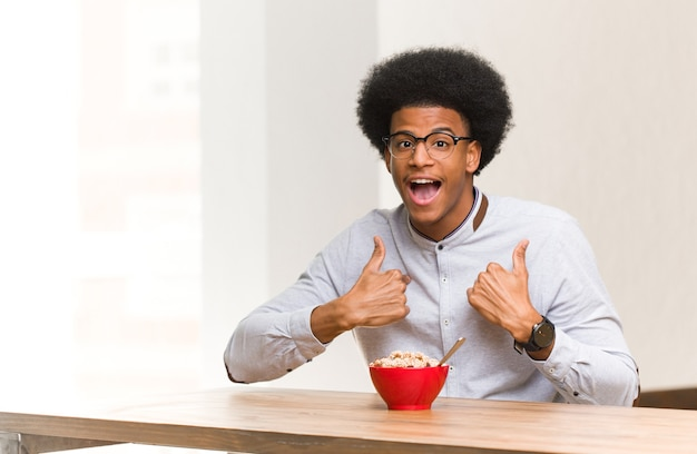Young black man having a breakfast surprised, feels successful and prosperous