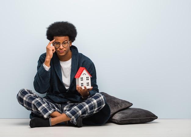 アイデアについて考えて床に座っている家のモデルを保持している若い黒人男性