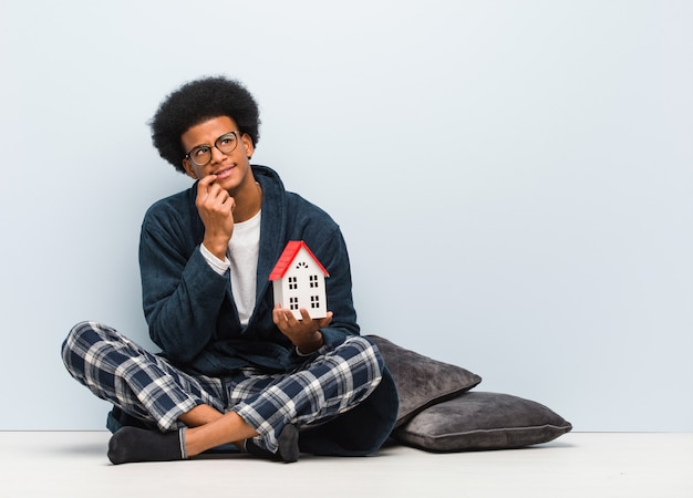 Young black man holding a house model sitting on the floor doubting and confused