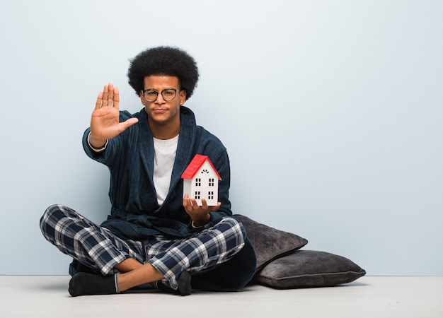 Young black man holding a house model sitting on the floor putting hand in front