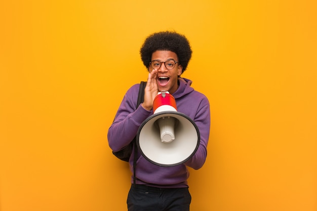 Young black man holdinga a megaphone shouting something happy to the front