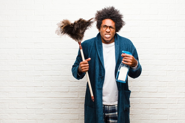 Young black man housekeeping with clean product
