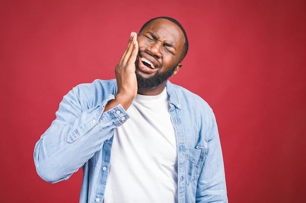 口を開いて赤い背景に分離された恐ろしい表情で顔に触れる若い黒人男性は、健康上の問題と歯の痛みに苦しんでいます。