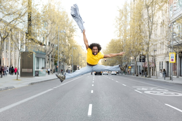 Young black man jumping energetically in the middle of the street in a big city. he has an afro hairstyle and dresses casually. space for text.