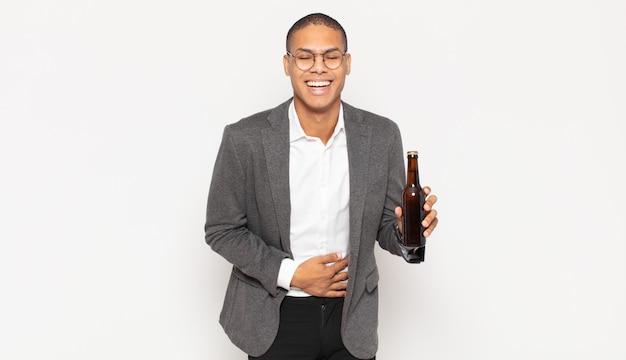 젊은 흑인 남자는 재미있는 농담에 크게 웃고, 행복하고 명랑하며, 즐겁게 지내고 있습니다.