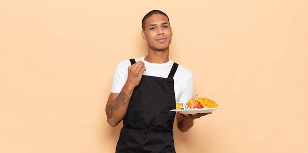 Молодой темнокожий мужчина выглядит высокомерным, успешным, позитивным и гордым, указывая на себя