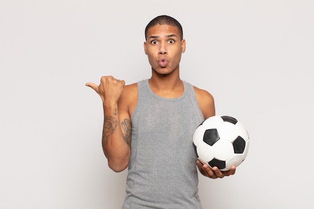 Young black man looking astonished in disbelief, pointing at object on the side and saying wow, unbelievable