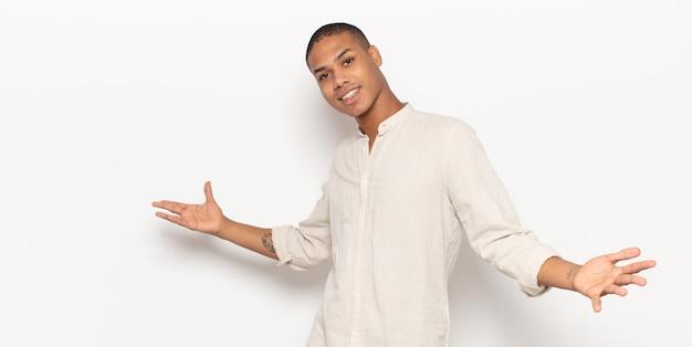 Молодой темнокожий мужчина выглядит счастливым, высокомерным, гордым и самодовольным, чувствуя себя номером один