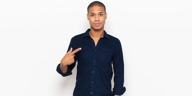 자랑스럽고 자신감 있고 행복하고 웃고 자신을 가리 키거나 번호 하나의 기호를 만드는 젊은 흑인 남자