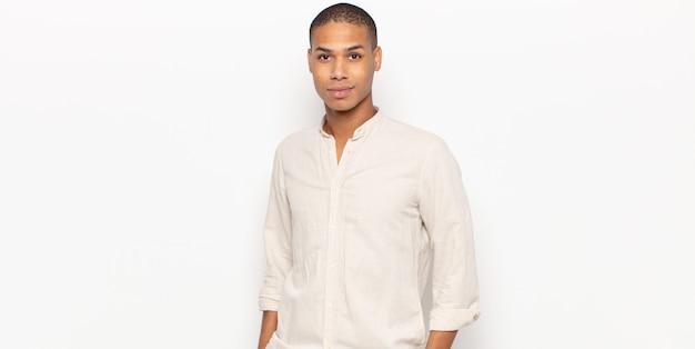 Молодой темнокожий мужчина выглядит гордым, уверенным, крутым, дерзким и высокомерным, улыбается и чувствует себя успешным