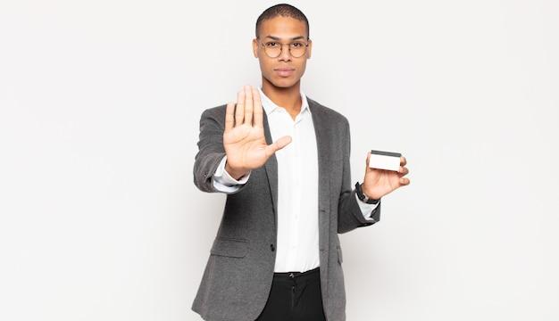 심각한, 선미, 불쾌하고 분노를 보여주는 젊은 흑인 남자가 열린 손바닥 만들기 중지 제스처를 보여주는