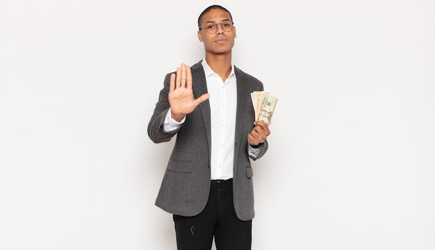 Young black man looking serious, stern, displeased and angry showing open palm making stop gesture