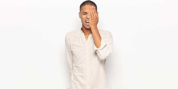 頭痛と片方の手が顔の半分を覆っている、眠くて退屈であくびをしているように見える若い黒人男性
