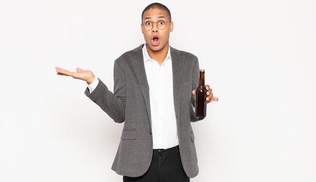 Молодой темнокожий мужчина выглядит удивленным и шокированным, с отвисшей челюстью держит объект открытой рукой сбоку
