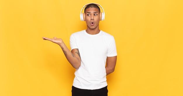 驚いてショックを受けた若い黒人男性が、横に開いた手でオブジェクトを持って顎を落とした