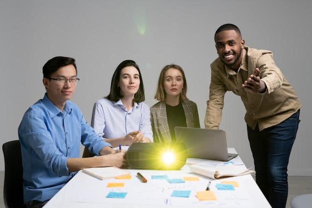 Молодой темнокожий мужчина указывает на вас, делая презентацию группе коллег, сидящих за столом с ноутбуком и проектором перед экраном
