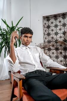 Молодой темнокожий мужчина позирует в кресле на фоне интерьера. стильная афро-мужская модель в белой рубашке позирует в современном интерьере в ресторане или студии.