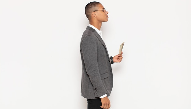 Young black man on profile view looking to copy space ahead, thinking, imagining or daydreaming
