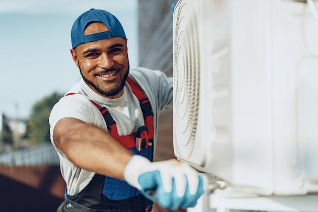 Молодой ремонтник чернокожего человека проверяя внешний блок кондиционера