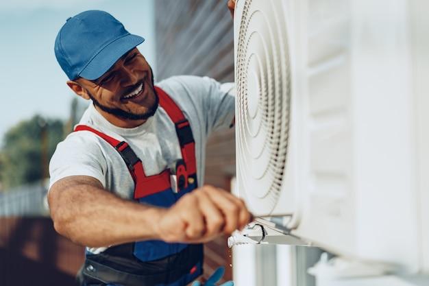 Молодой темнокожий ремонтник проверяет внешний кондиционер