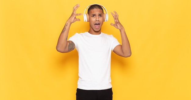 Young black man screaming with hands up in the air, feeling furious, frustrated, stressed and upset
