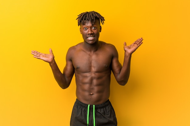 Young black man shirtless wearing swimsuit confused and doubtful raising him hands to hold a copy space.