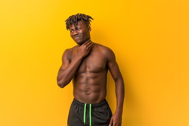上半身裸の若い黒人男性が水着を着ていると、ウイルスや感染症が原因で喉の痛みを感じます。