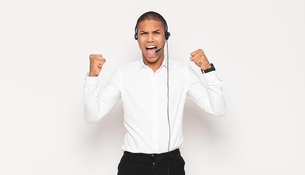Молодой черный мужчина агрессивно кричит с сердитым выражением лица или со сжатыми кулаками, празднуя успех