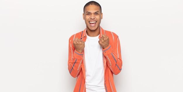 Молодой темнокожий мужчина торжествующе кричит, смеется и чувствует себя счастливым и возбужденным, празднуя успех