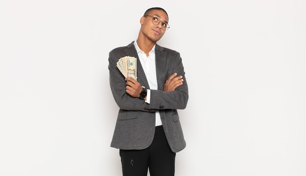 Young black man shrugging, feeling confused and uncertain, doubting with arms crossed and puzzled look